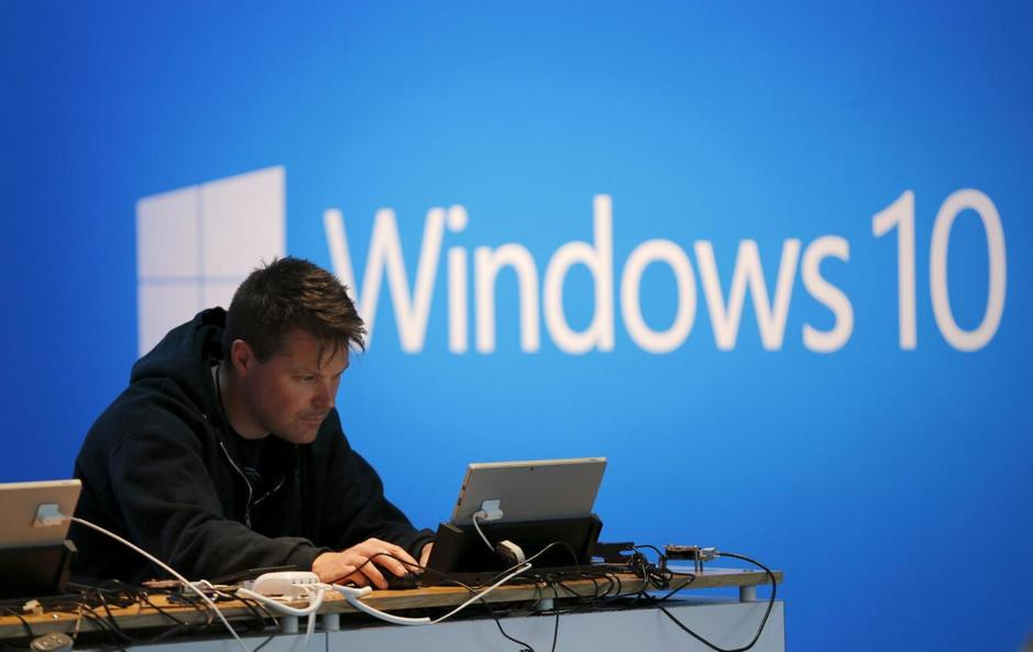 a-man-works-on-a-laptop-computer-near-a-windows-10-display-at-microsoft-build-in-san-francisco